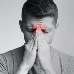 Man holding hands near his sinuses.