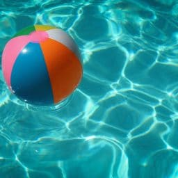 A beach ball floating in a pool.